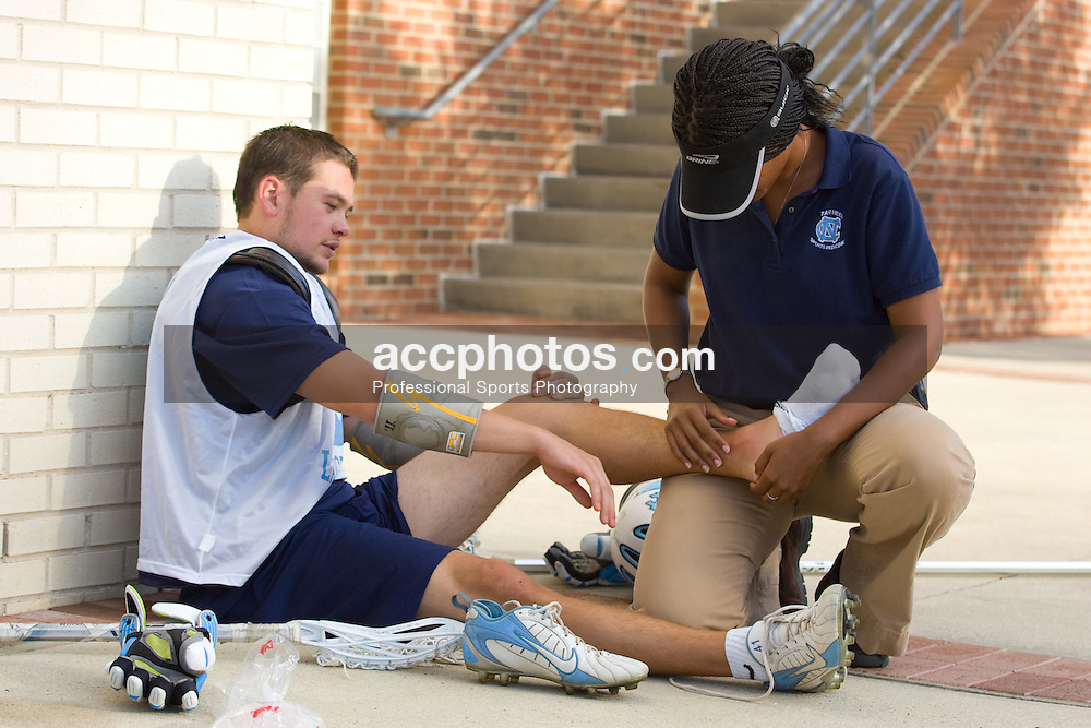 01 October 2007: North Carolina Tar Heels men's lacrosse member Kerry McCormick is treated by head trainer Nina Walker during a practice on the turf field in Chapel Hill, NC.