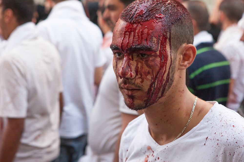 Young shiite muslim man, his face covered with his own blood, commemorating the Day of Ashura, Nabatieh, Lebanon (November 14, 2013).