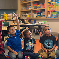 Students in Larrine Platero's kindergarten class raise their hands to participate in an activity on how to spell basic numbers at Catherine A. Miller Elementary School  in Churchrock Tuesday.
