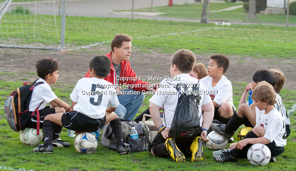Coach discussing soccer game strategy with boys age 10 during a rest break. Monroe Memorial Park St Paul Minnesota MN USA