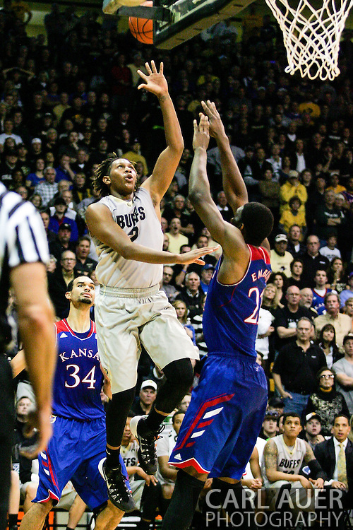 December 7th, 2013:  Colorado Buffaloes sophomore forward Xavier Johnson (2) floats a shot over Kansas Jayhawks freshman center Joel Embiid (21) in the second half of the NCAA Basketball game between the Kansas Jayhawks and the University of Colorado Buffaloes at the Coors Events Center in Boulder, Colorado