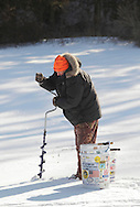 Middletown, New York - A man makes a hole in a frozen lake with an auger during the annual ice fishing contest at the Shawangunk Fish & Game Association on Jan. 23, 2011.