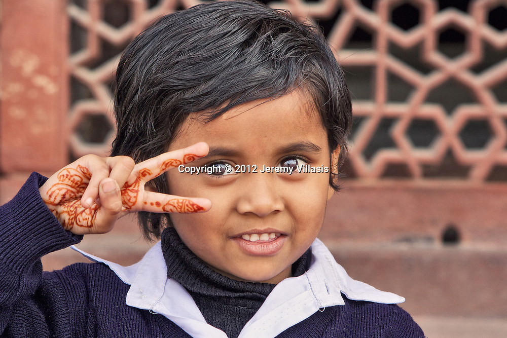 """A school girl with henna tattoo makes a """"peace"""" sign as she has her portrait taken in Humayun's Tomb. New Delhi, India."""