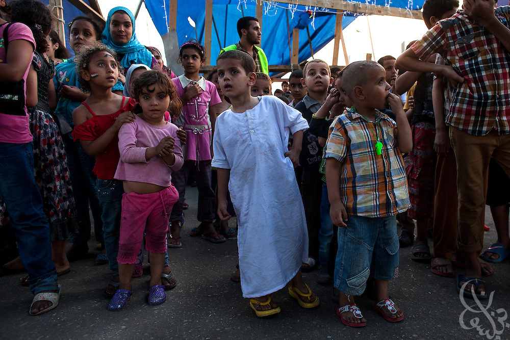 Children of the supporters of deposed Egyptian President Mohamed Morsi wait for their turn to enter a large playground August 12, 2013 at the entrance of an ongoing sit-in protest camp at the Rabaah al-Adawiya square in the eastern Nasr City district of Cairo, Egypt. The crowd at the camp, made up of men, women and children from various anti-coup coalition groups remains defiant in spite of threats by security officials to forcibly break up the camps soon. Opposing groups and human rights organizations have criticized what they see as exploitation of the children for political gain and use of women and children as human shields in order to deter action by security froces against the sit-in.