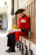 Chelsea Pensioner war veteran reading at the Royal Hospital in Chelsea, London