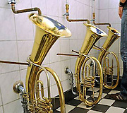 Trombones and very strange thrones: The wackiest toilets from around the globe<br /> <br /> There is no way anyone could describe these toilets as bog standard.<br /> This hilarious collection of toilets from around the world has become an internet sensation after they were posted on the blog Oddee.<br /> The pick of the bunch are a set of obscure urinals which resemble coffins complete with a foot flush that are found in a restaurant toilet in Bogota, Colombia. There is also a bizarre line of urinals that are shaped like brass instruments in a pub in Freiburg, South Germany.<br /> Another amusing latrine comes in the form of kitted out toilet that boasts a cushioned seat as well as a computer and phone close by designed clearly for the most avid workaholic.<br /> ©Exclusivepix