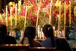 Huge display of flowers and candles under statue of Virgin Purificada, Church of Santa Clara, Cuzco, Peru, South America