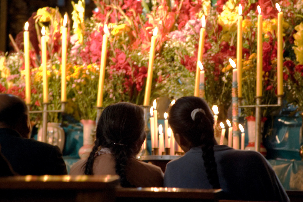 Huge display of flowers and candles under statue of Virgin Purificada, Church of Santa Clara, Cuzco, Peru, South America