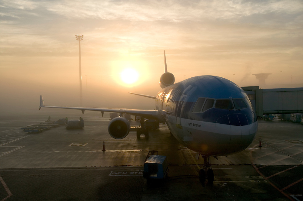 Europe, Netherlands, Amsterdam, Sunrise behind KLM passenger jet parked at Schipol International Airport on autumn morning.