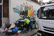 Workmen from Southwark Council clear away piles of street rubbish (garbage) left below a Stella Artois alcohol billboard.