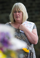 "© London News Pictures. 26/05/2013. Woolwich, UK.  Susan Metcalfe mother-in-law of Drummer Lee Rigby clutching a card reading ""daddy, from your little boy"" at the scene Lee Rigbys death during a visit to the scene  in Woolwick, London. Drummer Lee Rigby was murdered by two men in Woolwich town centre in what is being described as a terrorist attack. Photo credit: Ben Cawthra/LNP"