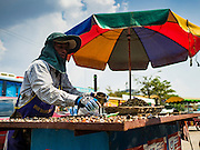 "15 FEBRUARY 2016 - ARANYAPRATHET, SA KAEO, THAILAND:  A Cambodian snack vendor on the Thai side of the border in Aranyaprathet, Thailand. Thais selling bottled water in the border town of Aranyaprathet, opposite Poipet, Cambodia, have reported a surge in sales recently. Cambodian officials told their Thai counterparts that because of the 2016 drought, which is affecting Thailand and Cambodia, there have been spot shortages of drinking water near the Thai-Cambodian and that ""water shortages in Cambodia had prompted people to hoard drinking water from Thailand.""    PHOTO BY JACK KURTZ"