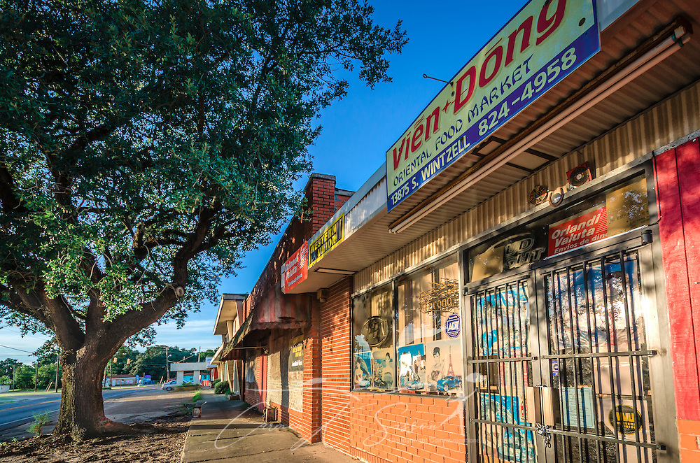 The sun sets on the Vien Dong Oriental Food Market, Aug. 15, 2015, in Bayou La Batre, Alabama. More than 33 percent of the city's population is Asian, due to an influx of Vietnamese, Cambodian, and Laotian refugees who fled to the U.S. in the 1970's to escape war and genocide in their homelands. (Photo by Carmen K. Sisson/Cloudybright)