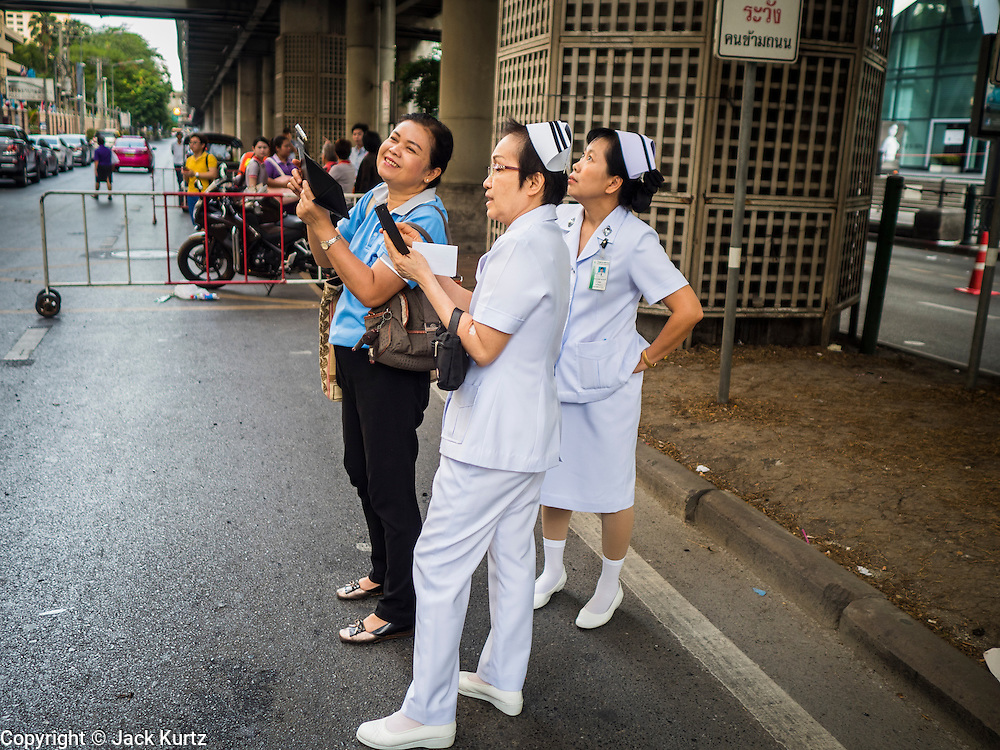 18 AUGUST 2015 - BANGKOK, THAILAND: Nurses from a nearby hospital photograph damage from an explosion at Erawan Shrine. An explosion at Erawan Shrine, a popular tourist attraction and important religious shrine in the heart of the Bangkok shopping district killed at least 20 people and injured more than 120 others, including foreign tourists, during the Monday evening rush hour. Twelve of the dead were killed at the scene. Thai police said an Improvised Explosive Device (IED) was detonated at 18.55. Police said the bomb was made of more than six pounds of explosives stuffed in a pipe and wrapped with white cloth. Its destructive radius was estimated at 100 meters.    PHOTO BY JACK KURTZ
