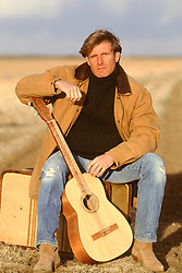 All American man sitting on a suitcase with a guitar outdoors