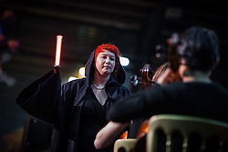 "© Licensed to London News Pictures . 06/12/2015 . Manchester , UK . Conductor JAEMI BLAIR LOEB uses a lightsaber to conduct a live orchestra playing music from Star Wars in the large exhibition hall . Fans attend Star Wars exhibition "" For the Love of the Force "" at Bowlers Exhibition Centre in Manchester . Photo credit : Joel Goodman/LNP"