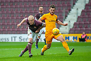 Craig Halkett (#26) of Livingston FC clears the ball ahead of Steven Naismith (#14) of Heart of Midlothian during the 4th round of the William Hill Scottish Cup match between Heart of Midlothian and Livingston at Tynecastle Stadium, Edinburgh, Scotland on 20 January 2019.