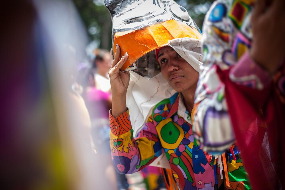 Un mujer paga promesa durante la festividad del Corpus Christi, representada en Venezuela a traves del ritual magico-religioso de los Diablos Danzantes. Los Diablos de Naiguata se identifican por pintar sus propios trajes y decorarlos con cruces, rayas y circulos, figuras que impiden que el maligno los domine. Las mascaras son en su gran mayoria animales marinos. Llevan escapularios cruzados, crucifijos y cruces de palma bendita. Naiguata, 30 Mayo 2013. (ivan gonzalez)