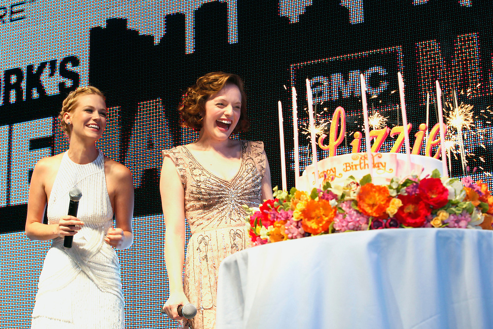 NEW YORK - JULY 25:   Fellow cast member January Jones looks on, left, as Elisabeth Moss, right, is presented with a surprise birthday cake before the live screening of AMC's Mad Men season 4 in New York's Times Square, presented by Chase Sapphire, Sunday, July 25, 2010. (Photo/Stuart Ramson for AMC)