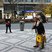 Globalisation: an Ecuadorian musician in a North American style feather headdress plays a flute while busking near Wenceslas Square in Prague, Czech Republic on 11 November 2014.