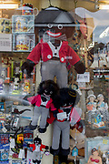 "Detail of a shop window selling seaside holiday trinkets including different sizes of Golliwogs, on 14th July 2017, at Scarborough, North Yorkshire, England. The golliwog is a black fictional character from the late 19th century depicting a rag doll. It was reproduced by commercial and hobby toy-makers as a children's toy and had great popularity in the UK and Australia into the 1970s. The doll has black skin, eyes rimmed in white, clown lips and frizzy hair and was seen, along with the teddy bear, as a suitable soft toy for a young boy. The image of the doll has become the subject of controversy as the Golliwog has been seen as a depiction of black people, accused along with pickaninnies, minstrels, mammy figures, and other caricatures as being racist. The golliwog has been described as ""the least known of the major anti-Black caricatures in the United States."
