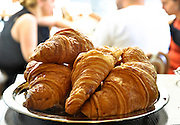 A plate with four croissants and out of focus people in the background