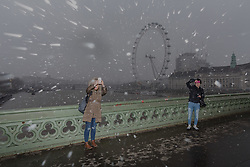 © Licensed to London News Pictures. 17/03/2018. London, UK. Tourists take selfie photographs of the London Eye from Westminster Bridge in London during snow and windy weather this morning. Photo credit: Vickie Flores/LNP