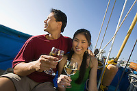 Couple dinking white wine on boat