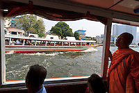 A Thai Buddhist monk on the Chao Praya River ferry in Bangkok, Thailand.