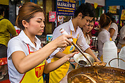 "17 OCTOBER 2012 - BANGKOK, THAILAND:  A soup vendor packages a ""to go"" order of vegan soup during the Vegetarian Festival food fair on Yaowarat Road in Chinatown in Bangkok. The Vegetarian Festival is celebrated throughout Thailand. It is the Thai version of the The Nine Emperor Gods Festival, a nine-day Taoist celebration celebrated in the 9th lunar month of the Chinese calendar. For nine days, those who are participating in the festival dress all in white and abstain from eating meat, poultry, seafood, and dairy products. Vendors and proprietors of restaurants indicate that vegetarian food is for sale at their establishments by putting a yellow flag out with Thai characters for meatless written on it in red.       PHOTO BY JACK KURTZ"