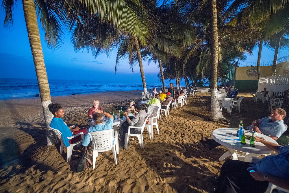 Groups of people are seated at tables along the beach at a restaurant. Monrovia, Liberia