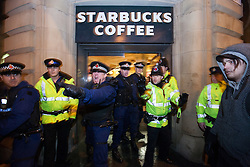 © Licensed to London News Pictures . 08/12/2012 . Manchester , UK . Police hold back protesters after a number forced their way in to the branch . UKUncut hold a demonstration against corporate tax avoidance outside a branch of Starbucks on St Ann's Square in Manchester City Centre today (8th December 2012) . Photo credit : Joel Goodman/LNP
