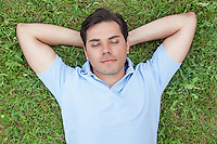 Young man with hands behind head lying on grass