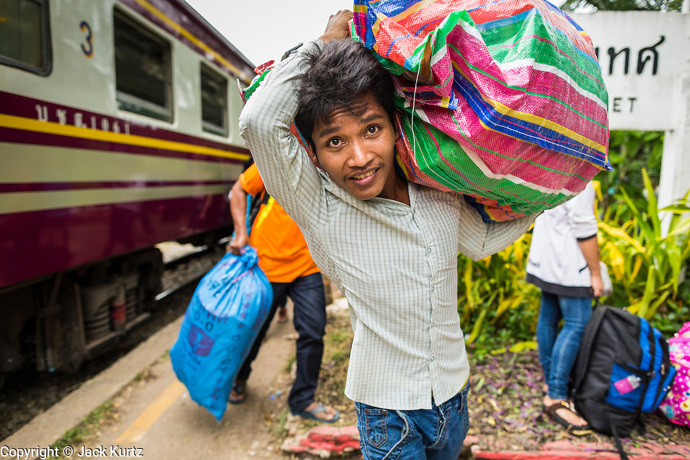 16 JUNE 2014 - ARANYAPRATHET, THAILAND: A Cambodian migrant carries his possessions on his back after getting off a train at the end of the train line in Aranyaprathet, Thailand. More than 150,000 Cambodian migrant workers and their families have left Thailand since June 12. The exodus started when rumors circulated in the Cambodian migrant community that the Thai junta was going to crack down on undocumented workers. About 40,000 Cambodians were expected to return to Cambodia today. The mass exodus has stressed resources on both sides of the Thai/Cambodian border. The Cambodian town of Poipet has been over run with returning migrants. On the Thai side, in Aranyaprathet, the bus and train station has been flooded with Cambodians taking all of their possessions back to Cambodia. PHOTO BY JACK KURTZ