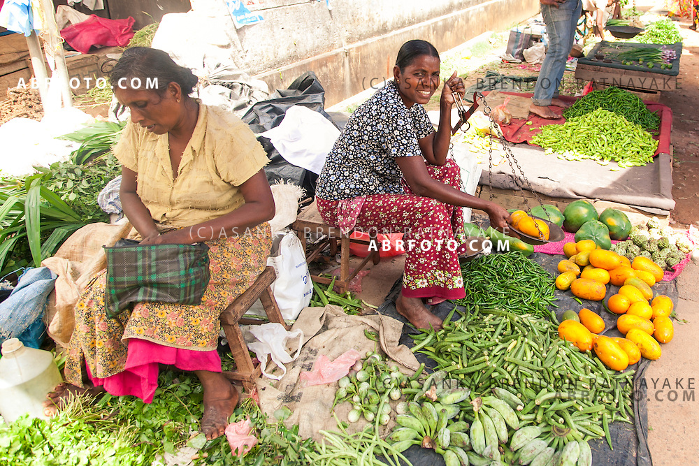 Two women sell vegtables at a village market in NegomboNegombo is a major city in Sri Lanka, located on the west coast of the island and at the mouth of the Negombo Lagoon