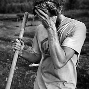 Gray T. wipes his brow while hoeing rows of beds during a Crop Mob, an activity in which farmers from different farms get together to complete a major project at one location. The experience builds community, helps out fellow farmers with a great deal of work, while encouraging conversation, working together and the sharing of knowledge.