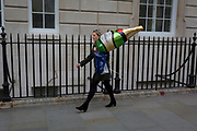 A woman carries a large helium-filled balloon in the shape of a generic champagne bottle, on 1st May, in London, England.