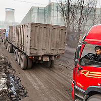 China, Shanxi Province, Datong, Drivers line up along dust-covered access road to deliver coal to Datong No. 2 Power Station