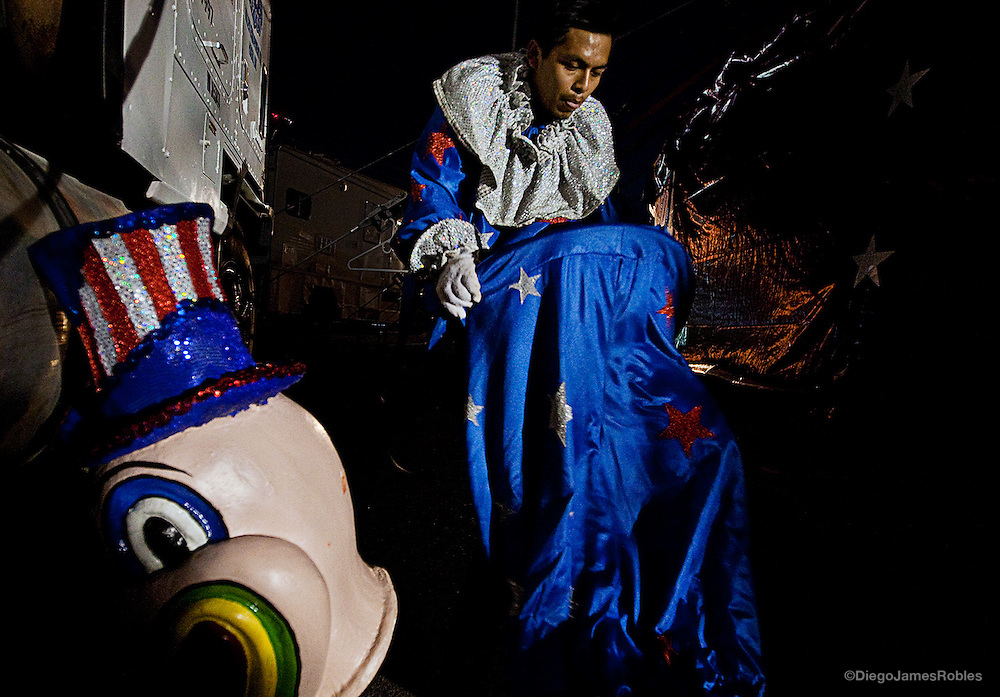 A hired hand, whose primary duty is assembling and disassembling the circus tent, struggles to put on a baggy clown costume moments before the final parade of the night's show, on Tuesday, March 24, 2009. In the chaotic circus life, most participants have multiple jobs and responsibilities, often working from dawn to dusk.