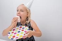 Cute girl eating birthday cake slice at home