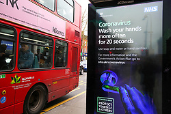 © Licensed to London News Pictures. 07/03/2020. London, UK. A bus drives past a Coronavirus public information campaign poster in London, which focuses on hand washing. Forty two more people have tested positive of the virus, taking the total to 206 in the UK. Photo credit: Dinendra Haria/LNP