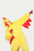 Playful young man in chicken suit against gray background
