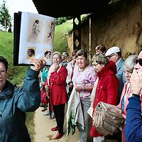 Nederland, Maastricht, 13 juli 2015.<br /> De neaderthalersite aan de rand van golfbaan Dousberg is na lange vertraging open.De gids en geinteresseerden verzamelen bij de brasserie van Maastricht Golf, waana te voet over de golfbaan de oversteek wordt gemaakt naar de neanderthalersite, grondgebied Veldwezelt.<br /> Op de foto:De toegangpoort/hek tot de Archeologische vindplaats Veldwezelt Hezerwater is versierd met o.a. figuurtjes met Neanderthalers en de weg naar de site toe versierd met figuratieve  dieren en Neanderthalers uit de betreffende periode op ware grootte.<br /> De gids geeft uitleg.<br /> Foto: Jean-Pierre Jans