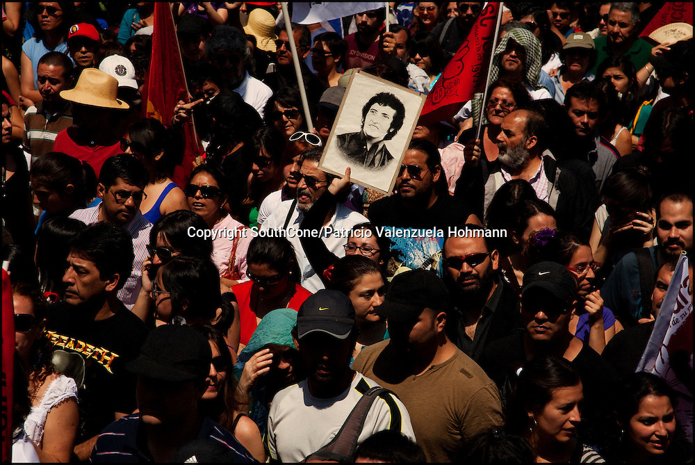 A woman hold a picture of Victor Jara.<br /> After 36 years, Chile's most popular folk singer, Victor Jara was mourned and buried. About 10.000 people attended to his vigil and funeral. Victor Jara was assassinated on September 15 1973 by Pinochet`s military officials of at least 43 gunshots and massive beatings. His 1973 funeral had to be made in private because of military restrictions.