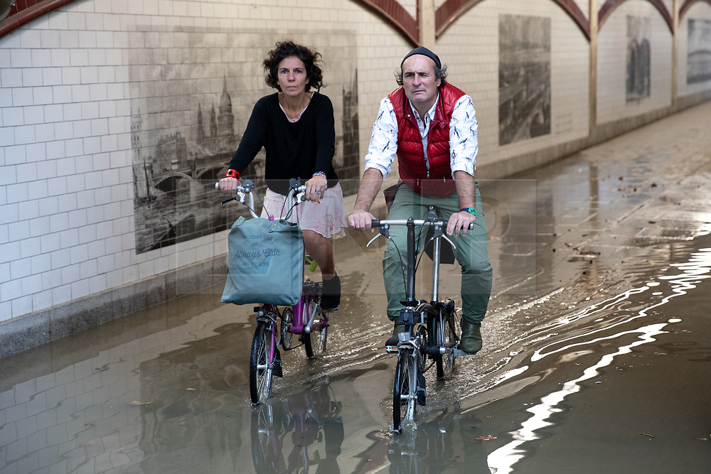 © Licensed to London News Pictures. 30/09/2019. London, UK. Cyclists negotiate a large area of water caused by flooding under a bridge near Blackfriars in Central London. Heavy rainfall is forecast for early this week. Photo credit : Tom Nicholson/LNP