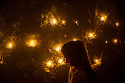 "4th December 2014, New Delhi, India. A woman passes in front of a wall lit by candles left by believers who come to pray, make offerings and ask for wishes to be granted by Djinns in the ruins of Feroz Shah Kotla in New Delhi, India on the 4th December 2014<br /> <br /> PHOTOGRAPH BY AND COPYRIGHT OF SIMON DE TREY-WHITE a photographer in delhi<br /> + 91 98103 99809. Email: simon@simondetreywhite.com<br /> <br /> People have been coming to Firoz Shah Kotla to leave written notes and offerings for Djinns in the hopes of getting wishes granted since the late 1970's. Jinn, jann or djinn are supernatural creatures in Islamic mythology as well as pre-Islamic Arabian mythology. They are mentioned frequently in the Quran  and other Islamic texts and inhabit an unseen world called Djinnestan. In Islamic theology jinn are said to be creatures with free will, made from smokeless fire by Allah as humans were made of clay, among other things. According to the Quran, jinn have free will, and Iblis abused this freedom in front of Allah by refusing to bow to Adam when Allah ordered angels and jinn to do so. For disobeying Allah, Iblis was expelled from Paradise and called ""Shaytan"" (Satan).They are usually invisible to humans, but humans do appear clearly to jinn, as they can possess them. Like humans, jinn will also be judged on the Day of Judgment and will be sent to Paradise or Hell according to their deeds. Feroz Shah Tughlaq (r. 1351–88), the Sultan of Delhi, established the fortified city of Ferozabad in 1354, as the new capital of the Delhi Sultanate, and included in it the site of the present Feroz Shah Kotla. Kotla literally means fortress or citadel. 4th December 2014, New Delhi, India. A woman stands by a wall covered with candles as offerings to Djinns in the ruins of Feroz Shah Kotla in New Delhi, India on the 4th December 2014<br /> <br /> PHOTOGRAPH BY AND COPYRIGHT OF SIMON DE TREY-WHITE a photographer in delhi<br /> + 91 98103 99809. Email: simon@simondetreywhite.com<br /> <br /> People have been coming to Firoz Shah Kot"