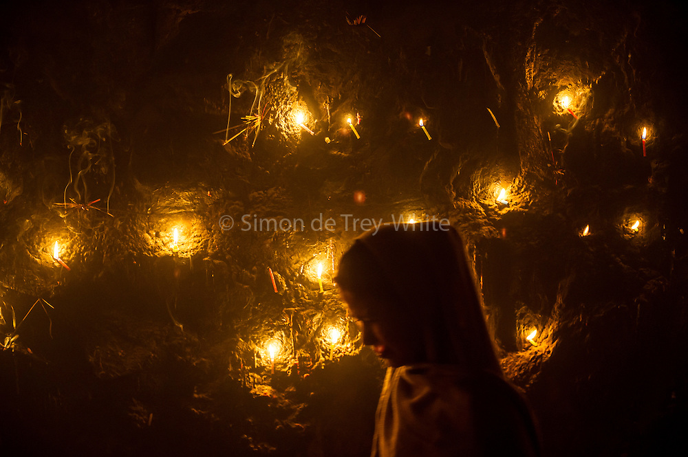 4th December 2014, New Delhi, India. A woman passes in front of a wall lit by candles left by believers who come to pray, make offerings and ask for wishes to be granted by Djinns in the ruins of Feroz Shah Kotla in New Delhi, India on the 4th December 2014<br /> <br /> PHOTOGRAPH BY AND COPYRIGHT OF SIMON DE TREY-WHITE a photographer in delhi<br /> + 91 98103 99809. Email: simon@simondetreywhite.com<br /> <br /> People have been coming to Firoz Shah Kotla to leave written notes and offerings for Djinns in the hopes of getting wishes granted since the late 1970's. Jinn, jann or djinn are supernatural creatures in Islamic mythology as well as pre-Islamic Arabian mythology. They are mentioned frequently in the Quran  and other Islamic texts and inhabit an unseen world called Djinnestan. In Islamic theology jinn are said to be creatures with free will, made from smokeless fire by Allah as humans were made of clay, among other things. According to the Quran, jinn have free will, and Iblis abused this freedom in front of Allah by refusing to bow to Adam when Allah ordered angels and jinn to do so. For disobeying Allah, Iblis was expelled from Paradise and called &quot;Shaytan&quot; (Satan).They are usually invisible to humans, but humans do appear clearly to jinn, as they can possess them. Like humans, jinn will also be judged on the Day of Judgment and will be sent to Paradise or Hell according to their deeds. Feroz Shah Tughlaq (r. 1351&ndash;88), the Sultan of Delhi, established the fortified city of Ferozabad in 1354, as the new capital of the Delhi Sultanate, and included in it the site of the present Feroz Shah Kotla. Kotla literally means fortress or citadel. 4th December 2014, New Delhi, India. A woman stands by a wall covered with candles as offerings to Djinns in the ruins of Feroz Shah Kotla in New Delhi, India on the 4th December 2014<br /> <br /> PHOTOGRAPH BY AND COPYRIGHT OF SIMON DE TREY-WHITE a photographer in delhi<br /> + 91 98103 99809. Email: simon@simondetreywhite.com<br /> <br /> People have been coming to Firoz Shah Kot
