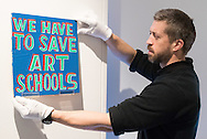A gallery technician hangs an artwork pleading the case for art in schools at the preview for the It&rsquo;s Our World charity auction at Christie's, Mayfair, London.<br /> Picture by Paul Davey/Focus Images Ltd +447966 016296<br /> 04/03/2016