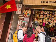 31 MARCH 2012 - HANOI, VIETNAM:   Tourists shop for handicrafts under a Vietnamese communist flag in the Old Quarter of Hanoi, Vietnam.  PHOTO BY JACK KURTZ