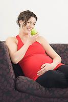 Pregnant woman eating apple on sofa portrait
